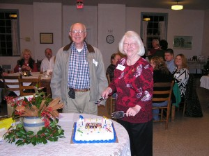 Jim & Janet with cake, Liza's arrangement & Janet Wilson in background
